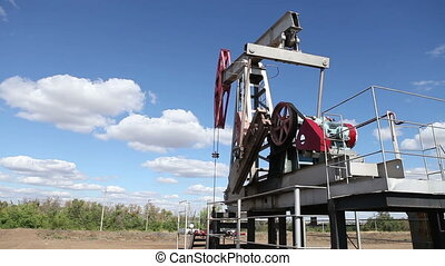 working oil pump on a background cloudy sky