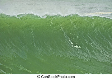 A wall of emerald green water moves toward the shore