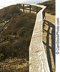 A wooden fence rail helps guide hikers to the Pacific...