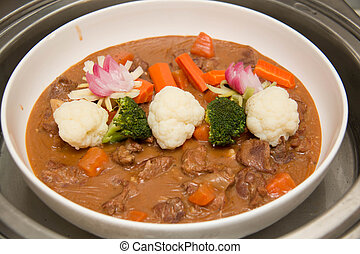 Beef stew in a white crock pot, ready to serve.