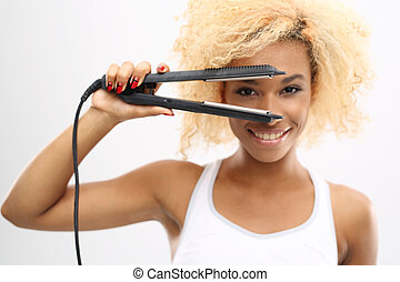 Hair straightener - Young girl straightens her hair with a...