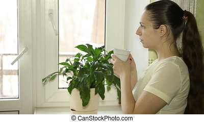 young girl drinking coffee and looking out the window