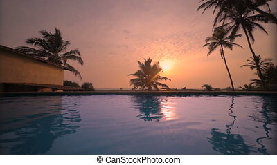 sea beach resort swimming pool with sunset reflection in...