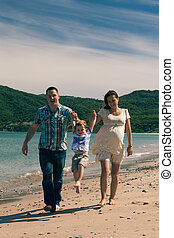 Happy family jumping and walking on the coast in Spain -...