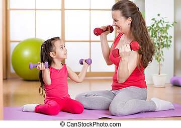 Woman and her child daughter doing fitness exercises with...