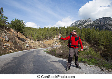 Hitchhiking traveler try to stop car on the mountain road