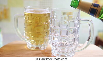 the beer is poured from a glass bottle into a large mug HD