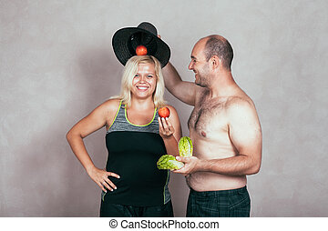 Cheerful corpulent couple with fruit and vegetable