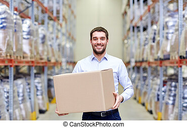happy man with cardboard parcel box at warehouse -...