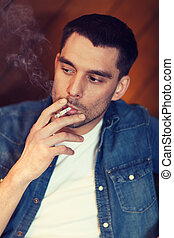 young man smoking cigarette at bar - people and bad habits...