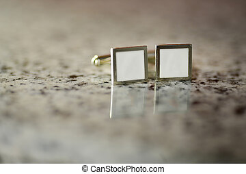 Silver cufflinks with white stone sitting on marble