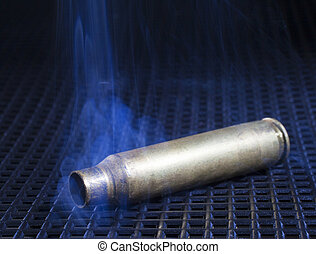 Ammo - Empty rifle casing on a black grate with smoke around