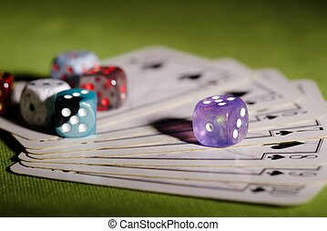 Purple dice on used playing cards - Horizontal photo of used...