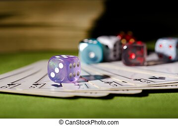 Used playing cards and purple dice - Horizontal photo of...