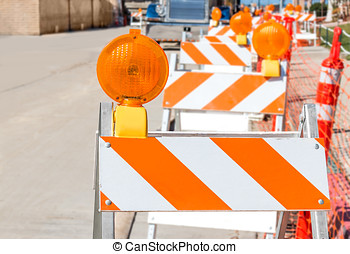 Row of bright orange and white striped construction warning...