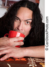 Tired man with coffee cup - Tired Latino man cradling red...
