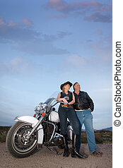 Motorcycle couple - Man and woman with motorcycle in the...