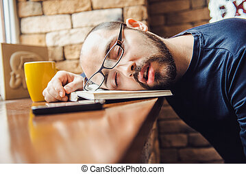 unshaven man in glasses tired, fell asleep at the table