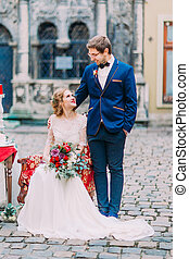 Handsome groom and bride look on each other with tenderness and love. Amazing old Lviv architecture on background