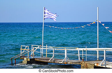 Flagstaff on a pier in the sea Flags of Greece