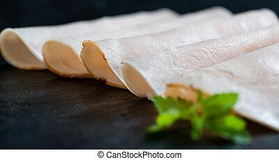 Sliced Chicken Breast fillet selective focus on slate