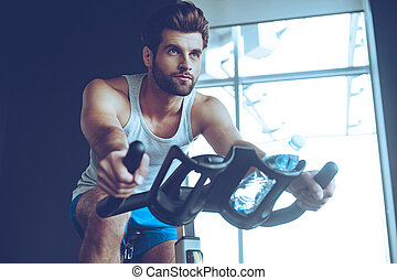 Confident cycler. Low angle view of young man in sportswear...
