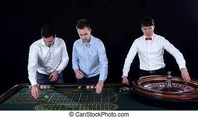 Young guys playing roulette in the casino. Black - Three...