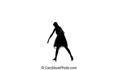 Young woman dancer starts dancing contemporary dance on white, silhouette, slow motion