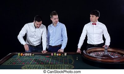 Young man playing roulette in the casino Dealer takes bets...