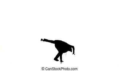 Young man jumps and stands on hands dancing breakdance,...