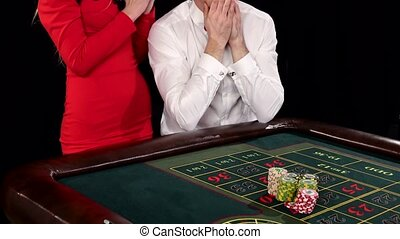 A rich elegant couple gambling in a casino. Black