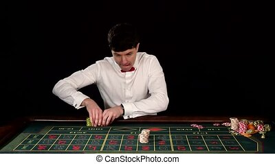 Man in a casino playing on the roulette. Black - Man in a...