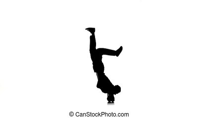 Young dancer man dancing breakdance moves on head, white,...