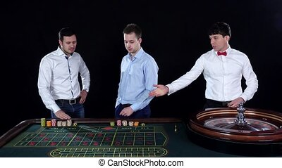 Man playing roulette in the casino Black - Three guys...