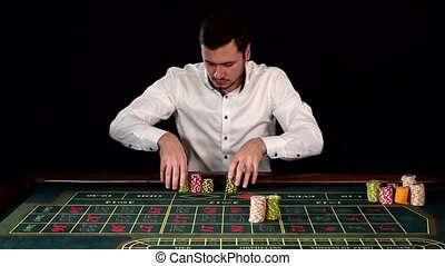 Man in a casino winning on the roulette. Black - Man in a...
