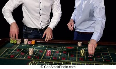 Two good-looking guy in the casino. Black - Two good-looking...