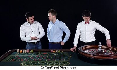 Three guys playing roulette in the casino. Black - Three...