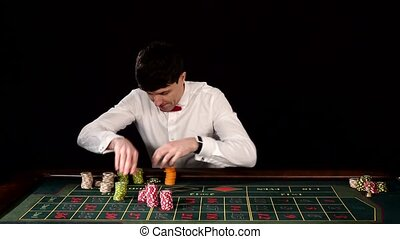 Young guy in the casino at the gaming table. Black - Poker...