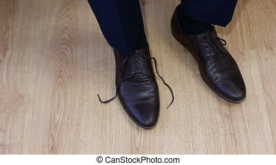 Man tying patent leather shoes formal and festive dressing....
