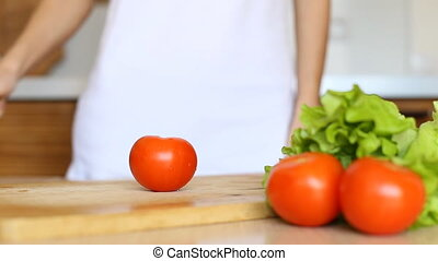 Woman hands slicing tomato in kitchen.