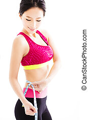 young Fitness woman measuring her belly