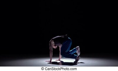 Talanted dancer in blue trousers starts dancing breakdance,...