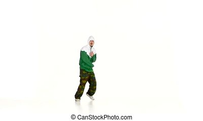 Modern dancer in jacket and hood dancing breakdance on...