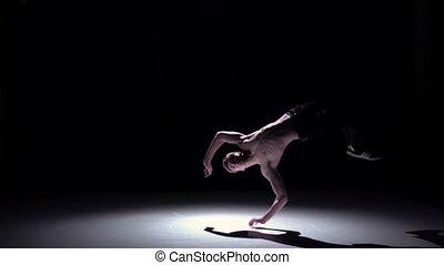 Blonde breakdancer man with doing handstand on black,...