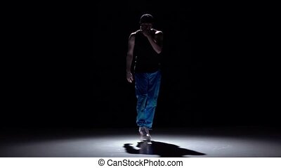 Talanted dancer in blue trousers dancing breakdance, on...