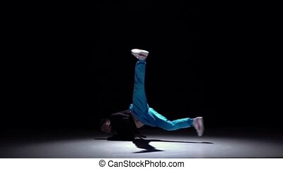 Stylish breakdance style dancer goes on dance, on black,...