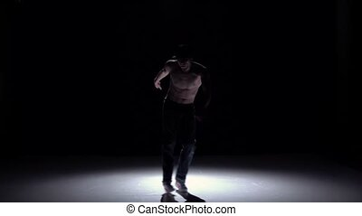 Breakdance dancer man in trousers, cap with torso dance on black, shadow, slow motion