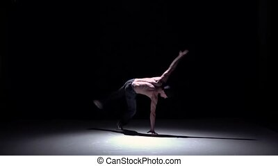 Breakdancer man in cap doing handstand on black, shadow,...