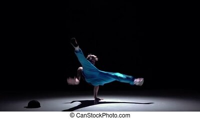 Dancer in blue trousers dancing breakdance on his hands,...