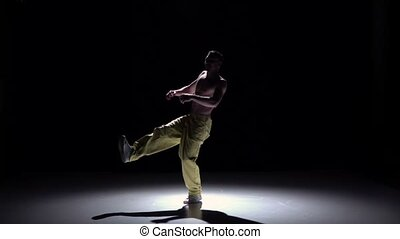 Breakdance dancer man in yellow trousers with torso dance on black, shadow, slow motion